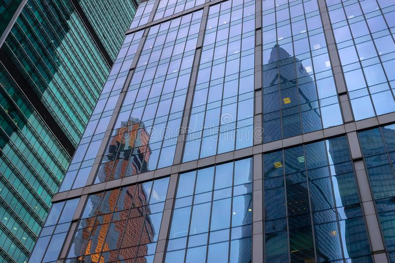 Glass and plastic office windows of a high skyscraper. Glass and plastic office windows of high skyscraper with reflection of tall buildings in the evening royalty free stock images