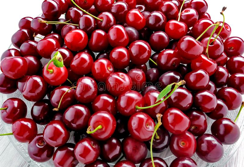 Glass plate of fresh cherry berries close-up on white background royalty free stock images
