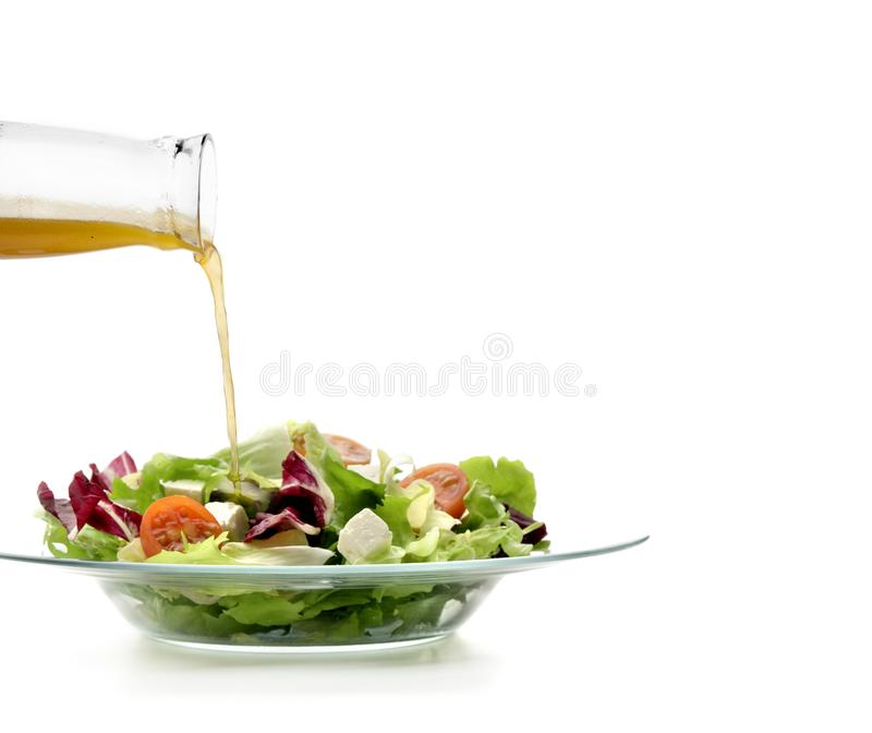 Glass plate with lettuce salad and a stream of olive oil falling on it stock image