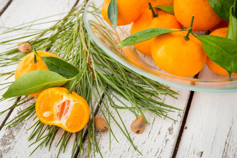 A glass plate of ripe orange clementine tangerines decorated wit stock photo