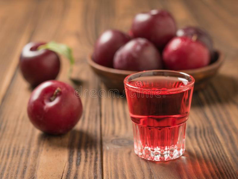 Glass with plum alcohol on the background of the bowl with ripe plums. Homemade alcoholic drink made from berries plum royalty free stock photography