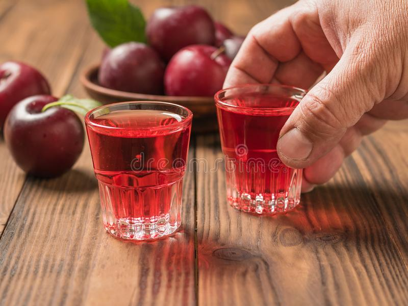 A glass of plum alcohol in a man`s hand on a wooden table. stock photography