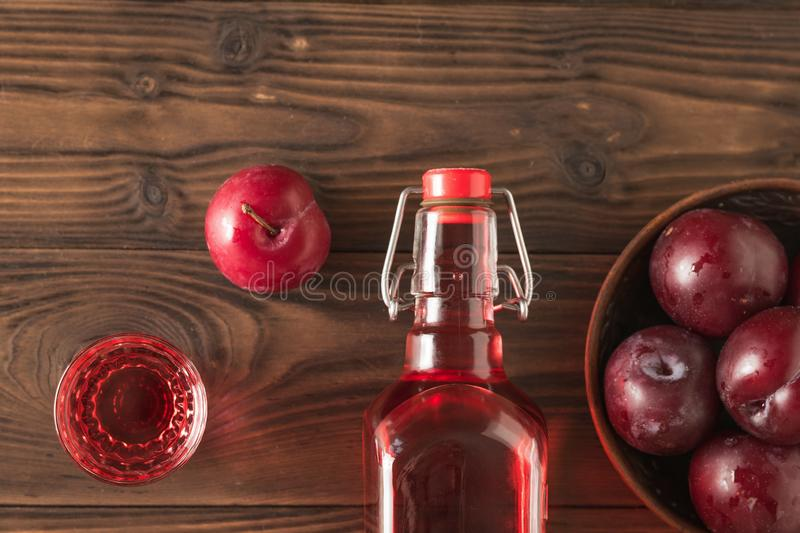 A glass of plum liqueur and plum berries on the village table. Flat lay. stock photos