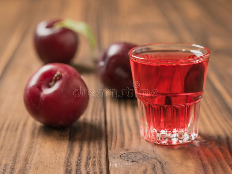 A glass of plum liqueur and plum berries on the village table. Homemade alcoholic drink made from berries plum stock photos