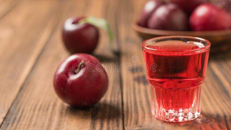 A glass of plum liqueur with a bowl of plums on a wooden table stock photography