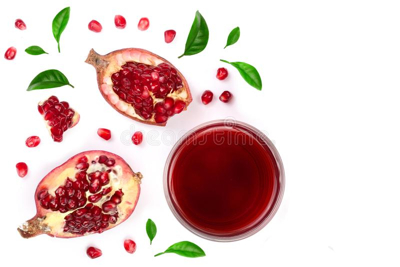 A glass of pomegranate juice with fresh pomegranate fruits decorated with leaves isolated on white background. Top view stock photos