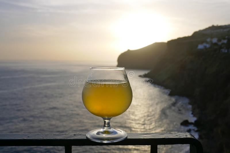 A glass of poncha at sunset on Madeira with stunning views of the rocky coastline. Poncha is a traditional alcoholic beverage from the island of Madeira royalty free stock image