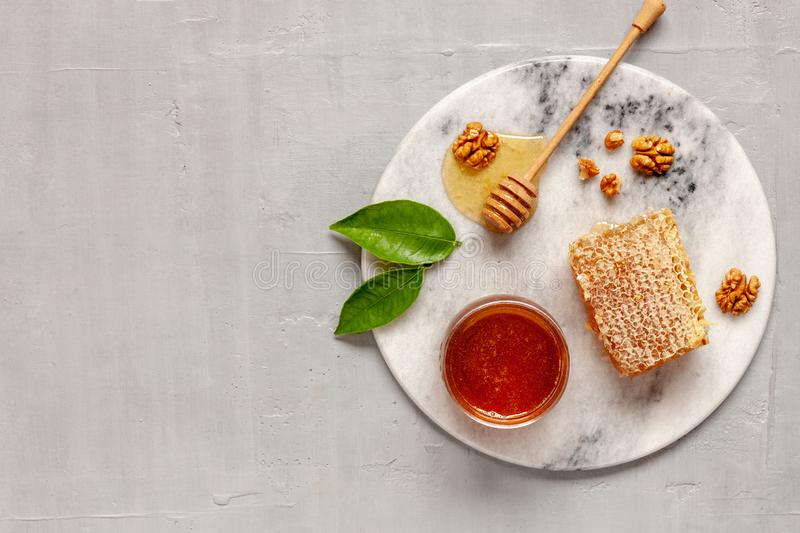 Glass pot with Fresh natural honey, honeycomb and walnuts on a stone board. Top view, close-up, flat lay on gray concrete royalty free stock photography
