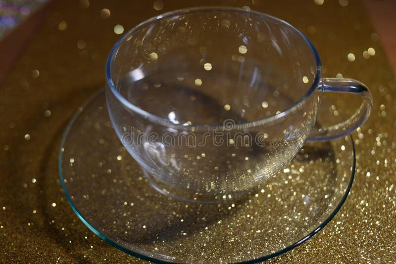 Glass pot with saucer on gold blur background. For print on paper royalty free stock image