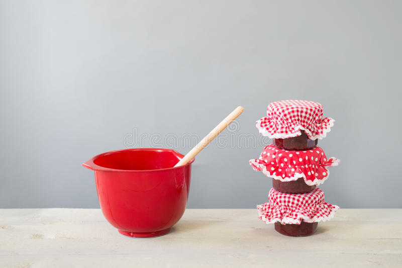 Glass pots jam and red bowl. Preparing red fruit jam with three glass pots of home made jam royalty free stock images
