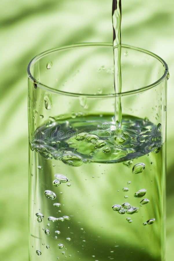 Glass and pouring water royalty free stock photography
