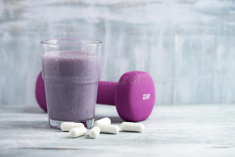Glass of Protein Shake with milk and blueberries. BCAA amino acids and a violet dumbbell in background. Sport nutrition. Rustic wooden background. Copy space royalty free stock image