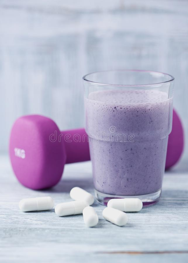 Glass of Protein Shake with milk and blueberries. BCAA amino acids and a violet dumbbell in background. Sport nutrition. Rustic wooden background. Copy space stock images