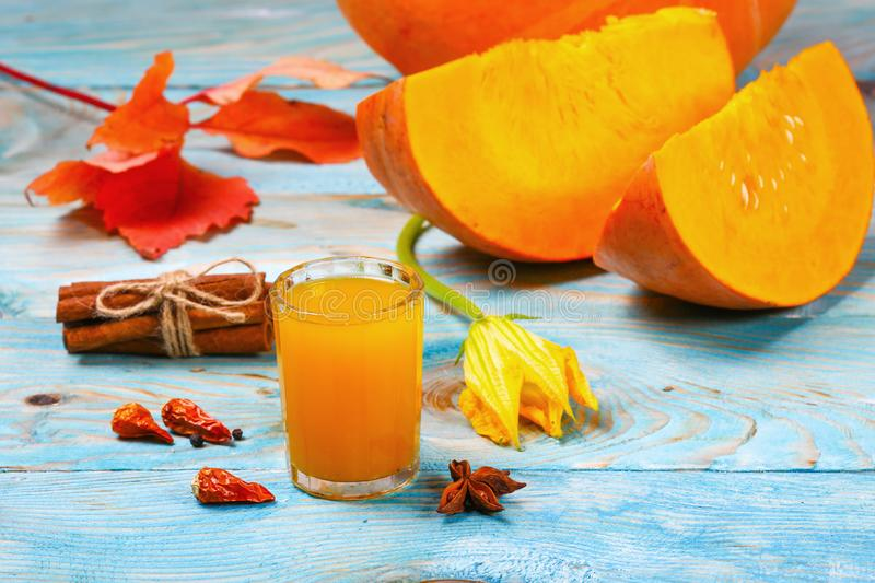 A glass of pumpkin juice placed on a table near the pumpkins. The new crop of pumpkins. Pumpkin juice on the table. Autumn harvest stock images