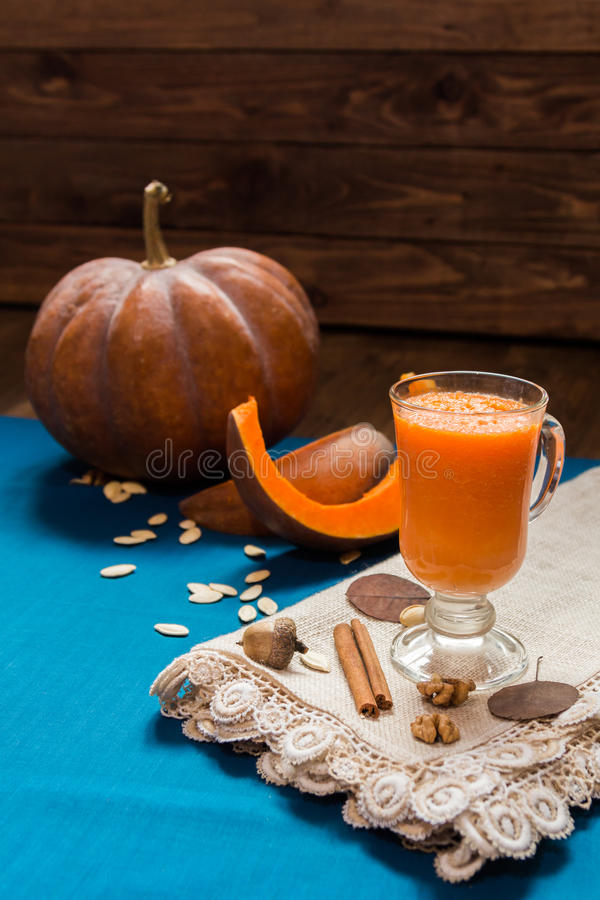A glass of pumpkin smoothies. On a blue background with pieces of pumpkin and walnuts royalty free stock images