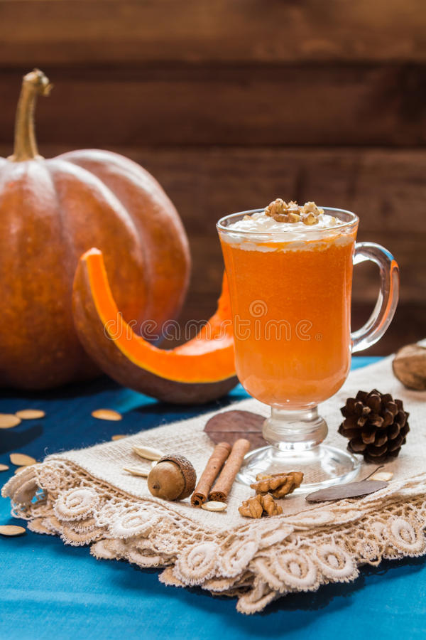 A glass of pumpkin smoothies. On a blue background with pieces of pumpkin and walnuts royalty free stock image