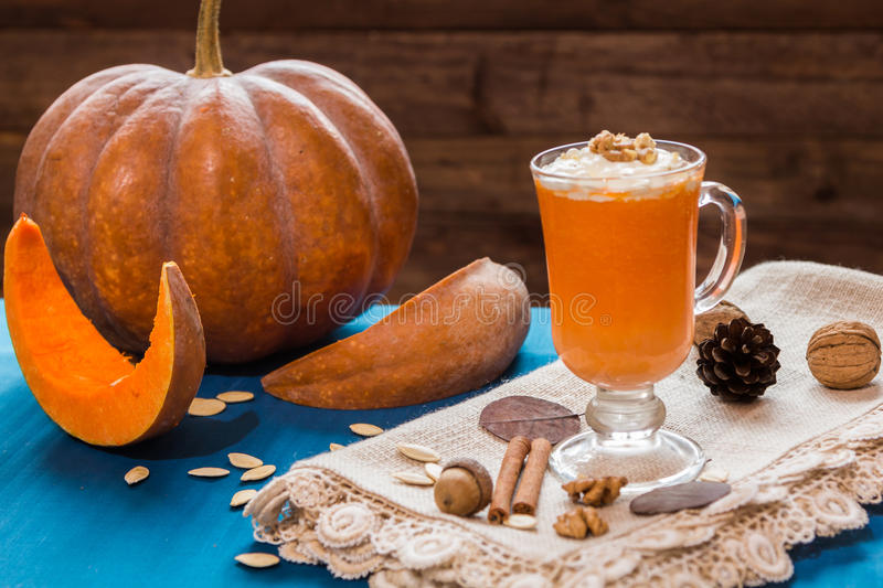 A glass of pumpkin smoothies. On a blue background with pieces of pumpkin and walnuts stock photo