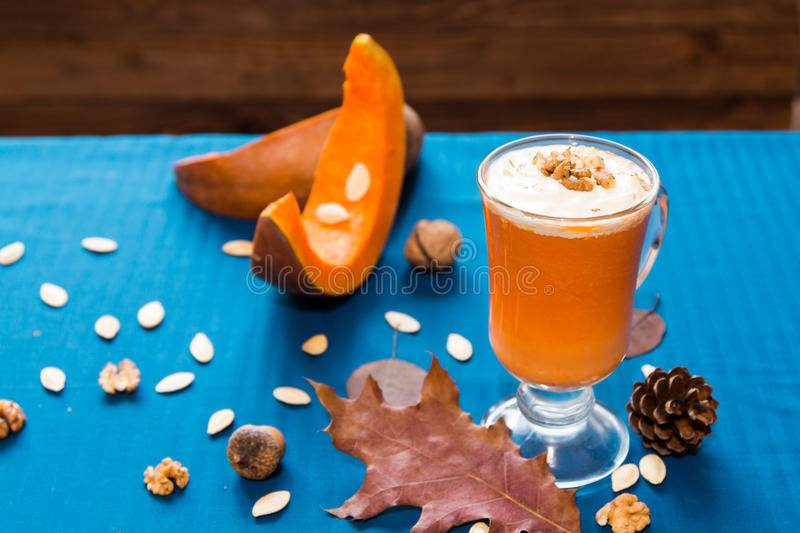A glass of pumpkin smoothies. On a blue background with pieces of pumpkin and walnuts stock image