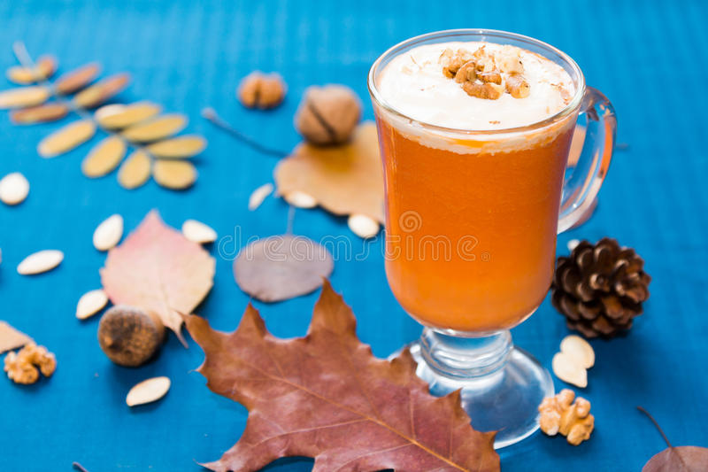 A glass of pumpkin smoothies. On a blue background with pieces of pumpkin and walnuts stock images