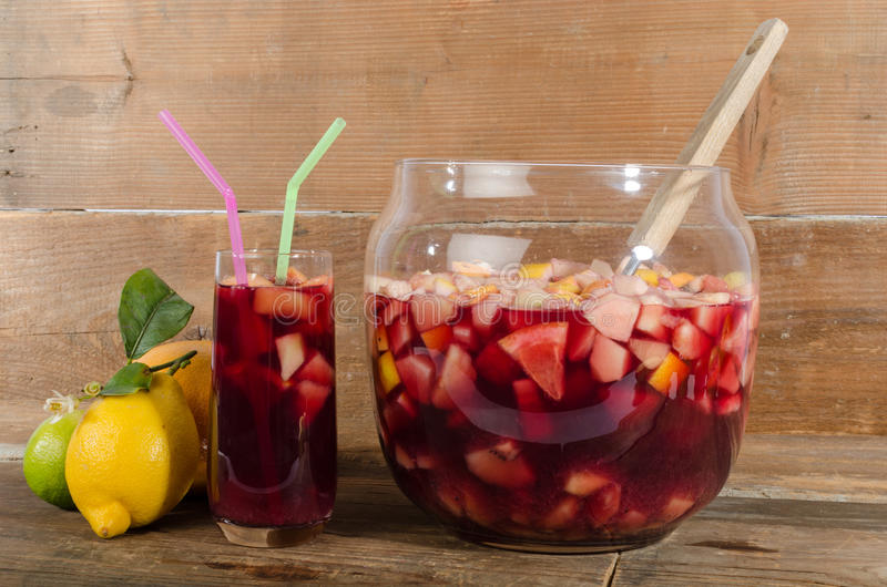 Glass and punch bowl of sangria. On wooden background royalty free stock image