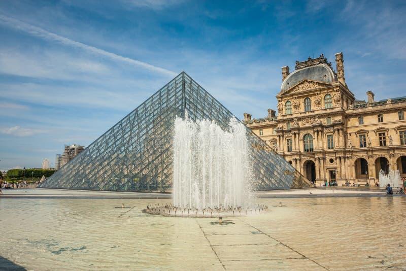 Glass pyramid och springbrunn på det Louvrekonstgallerit och museet arkivfoton
