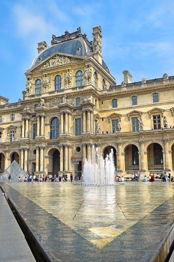 Glass pyramid och springbrunnen för Louvremuseet, Paris arkivfoto