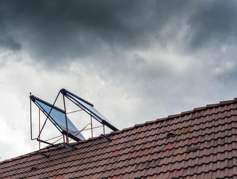 Glass rör för vattenvärmeapparat på residentual hustaköverkant arkivbild