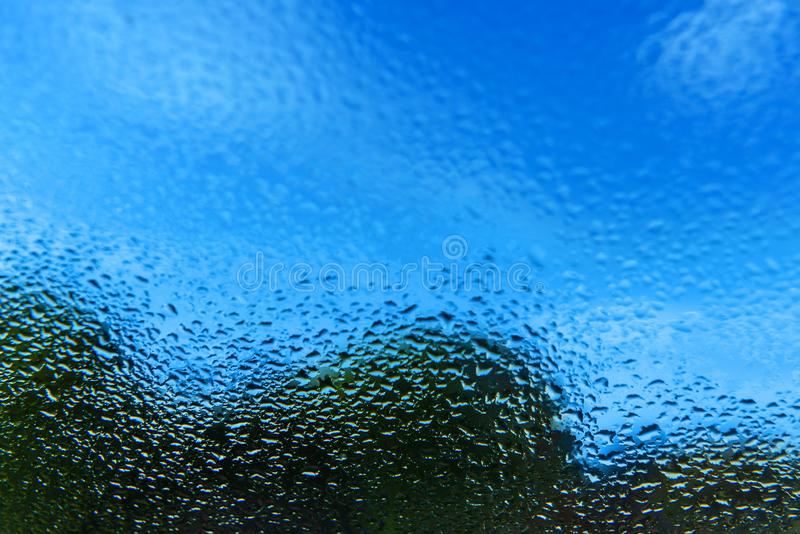 glass raindrops Utanför fönstret är en blå himmel med moln, och en grön skogsommar är bra väder arkivbilder