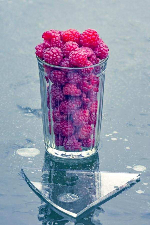 Glass with raspberries on ice stock images