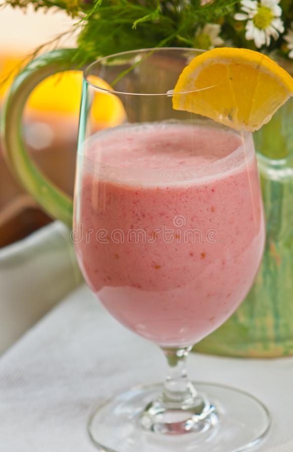 Glass of raspberry coconut smoothie with a slice of lemon. Front view, close up of a stemmed Glass of homemade, raspberry coconut smoothie with a slice of lemon royalty free stock photography