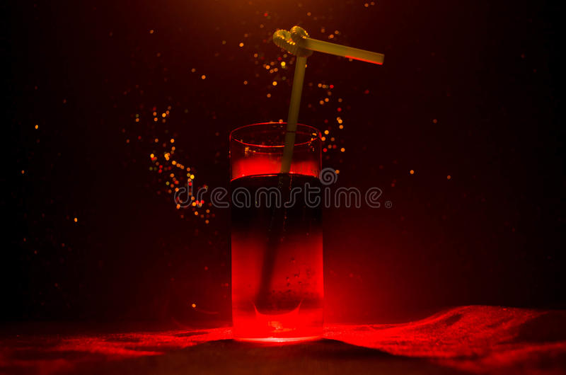 Glass of Red Alcoholic Cocktail on Dark Background with smoke and backlight. Fire hot coctail. Club concept. Glass of Red Alcoholic Cocktail on Dark Background stock images