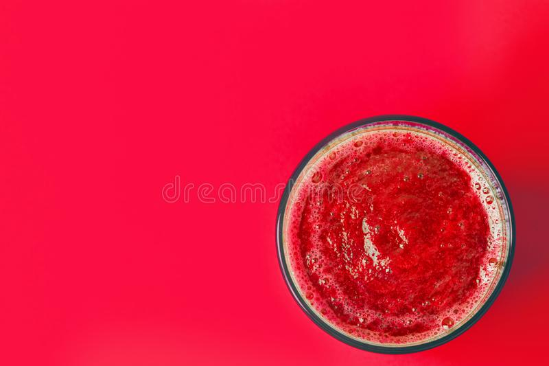Glass with red beet berries and fruits smoothie from strawberries raspberries currants bananas apples on same color background. Healthy vegan lifestyle detox stock photography