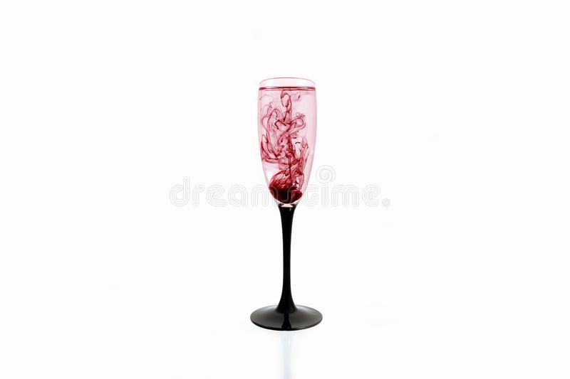 Glass red black wine white background close up fougere paint smoke streak purple stock image