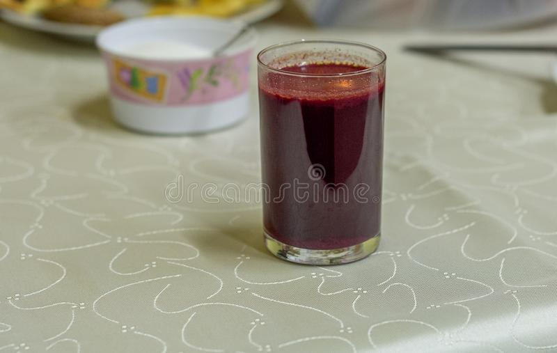 Glass of red borscht. On table with wedding tablecloth royalty free stock image