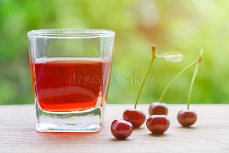 Glass with red cherry juice and a berries on a wooden table, illuminated by sunlight on a background of green garden in blur. royalty free stock photos