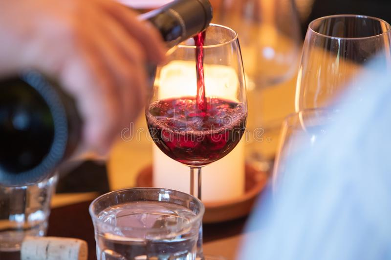 Glass of red clear wine wine tasting poor from a bottle against candle light royalty free stock image