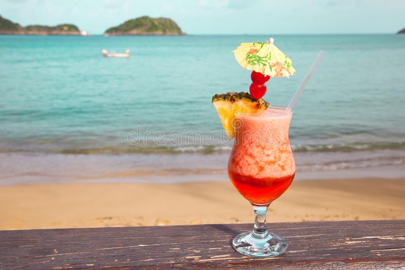 A glass with red cocktail pineapple with an umbrella on the background turquoise sea stock photos