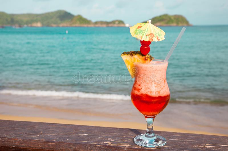 A glass with red cocktail pineapple with an umbrella on the background turquoise sea royalty free stock photography