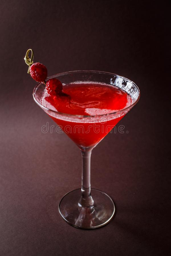 Glass of red cocktail with paspberries on elegant dark brown background stock image