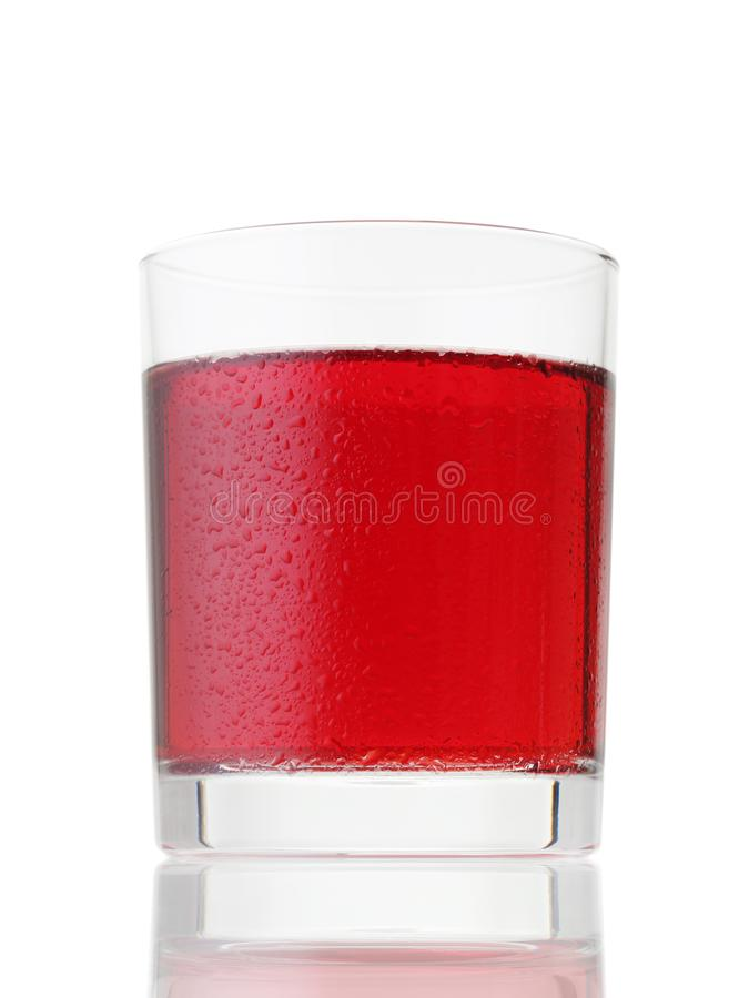 Glass of red drink covered by water drops on white stock photography