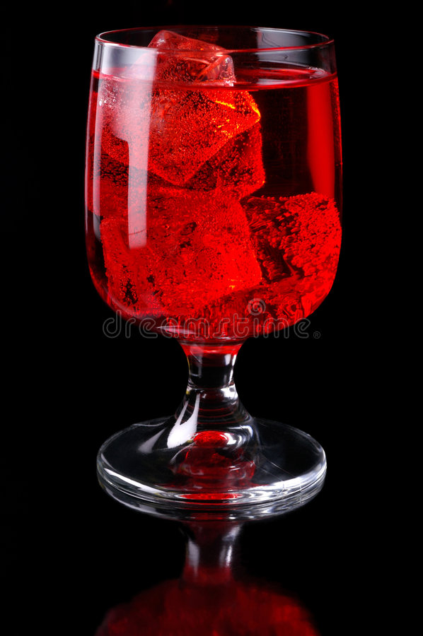 Glass of red drink with ice royalty free stock image