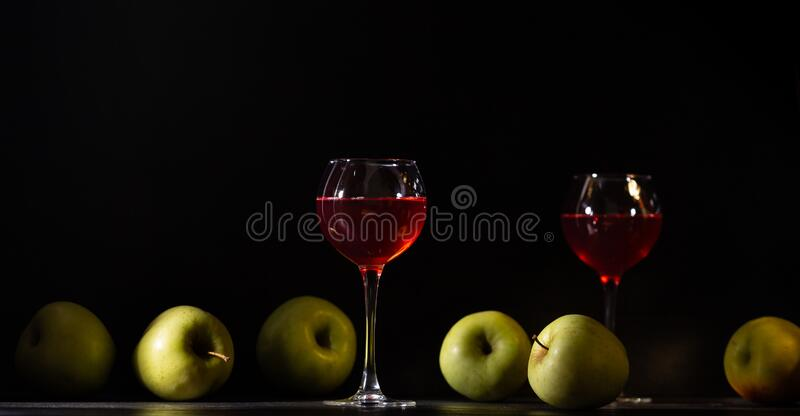 A glass of red fruit wine. Apples fresh crop, still life in a low key. Copy space. Banner for cafe, winery and restaurant royalty free stock image