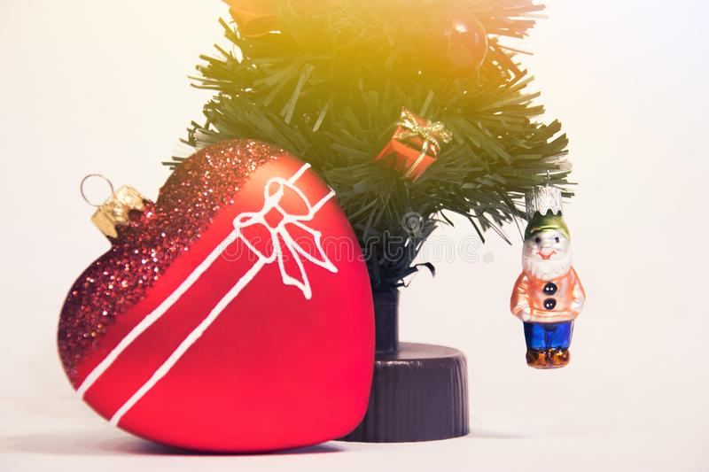 Glass red heart and Christmas decorative Christmas tree. Beautiful New Year Decorations. stock image