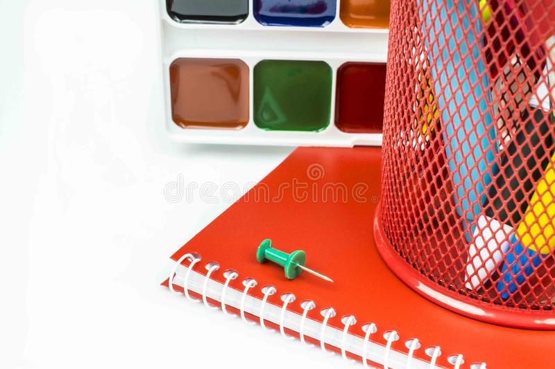 The red glass with pens of different colors, a red notebook, paints, a green button isolated on a white background. The glass of red with pens of different royalty free stock photos