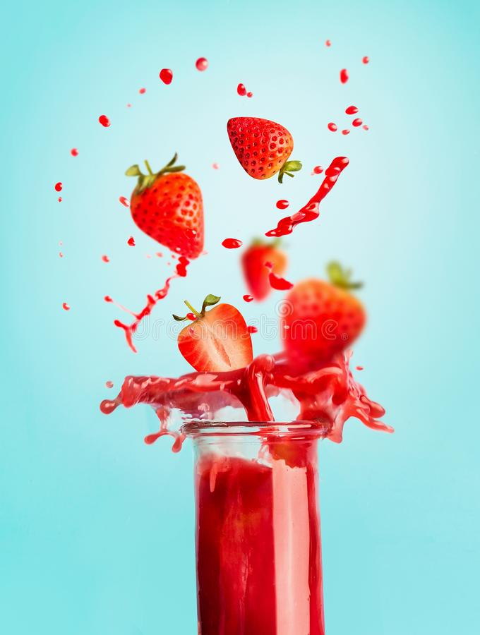 Glass of red strawberry splash summer beverage: smoothie or juice standing at blue background with copy space for your design, stock photo