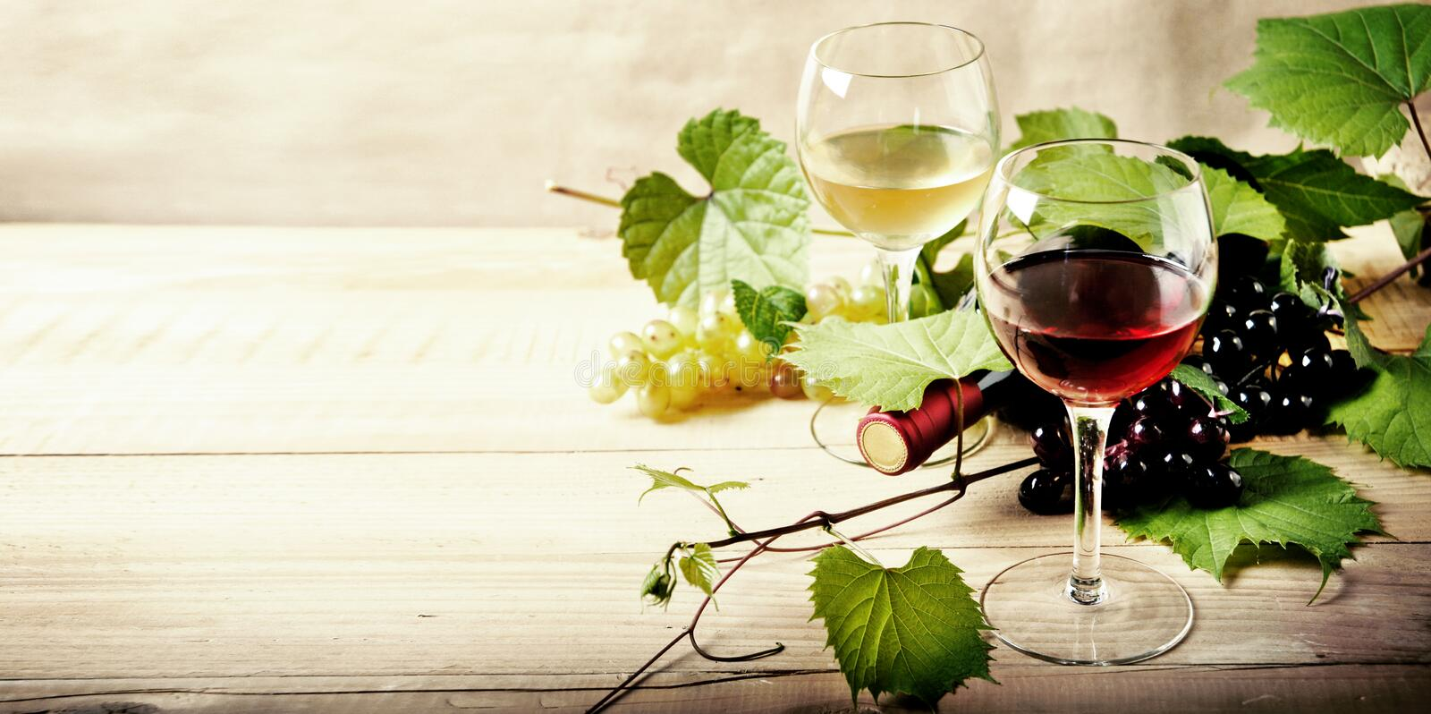 Glass of red and white wine, bottle and grape vine on vintage wooden table. stock photos