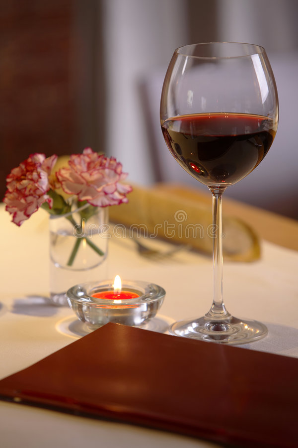 Glass Of Red Wine. On a table, alongside a menu or wine list, small burning candle, and two carnations in a glass of water royalty free stock image