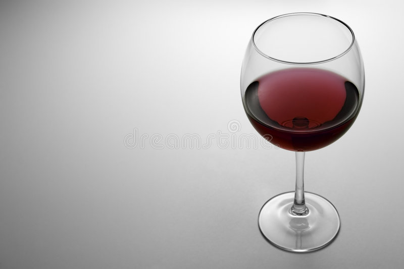 Glass of Red Wine 2. Glass containing red wine. Backlit white gradient background with Copy Space at the left royalty free stock photos