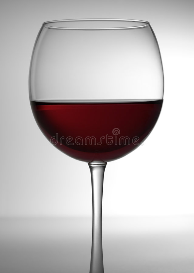 Glass of Red Wine 3. Wine glass profile with stem containing red wine. Close-up, backlit white background with horizon stock images