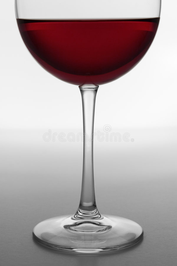 Glass of Red Wine 4. Bottom section of a wine glass containing red wine. Close-up, backlit white background with horizon stock image